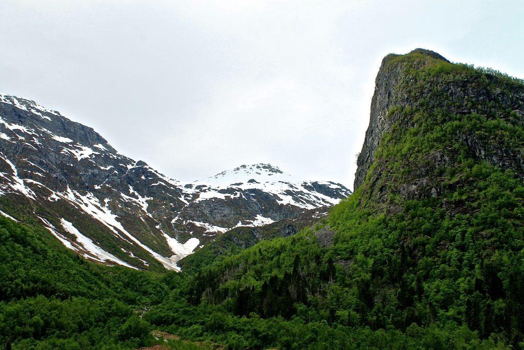 Fra Flatbrehytta går en på sti gjennom skog med skiene på sekken.