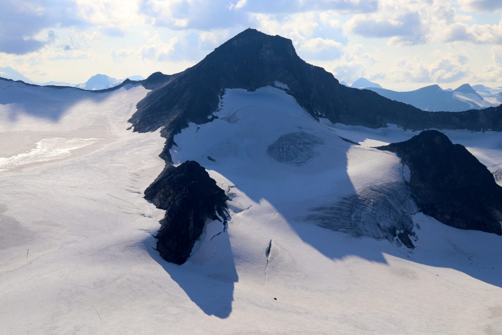 Søre- og Nørdre Hellstugubrahesten stikker opp av Hellstugubrean. Midtre Hellstugutinden (2.339 moh) bak.