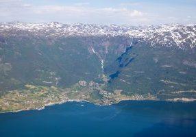 Lofthus i Sørfjorden sett fra Vardanuten. Fra Hardangervidda platået renner noen spektakulære fossefall; Bjørnabykset og Skrikjo.