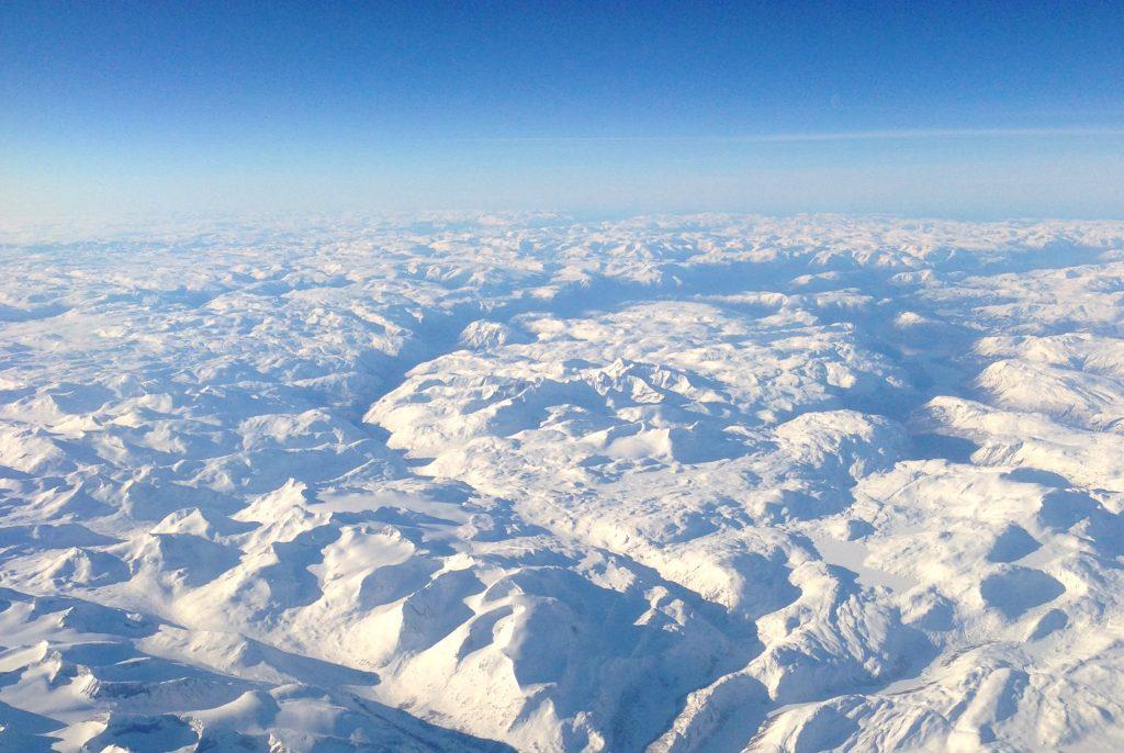 Hurrungane sett fra luften. Toppene skiller seg ut som alpine tinder midt i bildet.